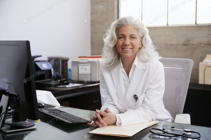 Senior female doctor sitting at desk in an office, portrait