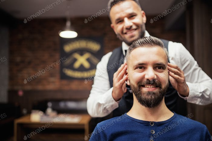 Hipster man client visiting haidresser and hairstylist in barber shop. Copy space.
