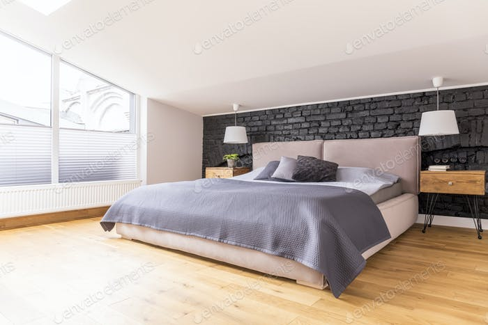 King-size bed between bedside cabinets