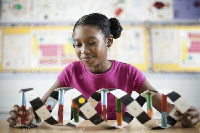 A girl in a science class holding a model of a helix structure.