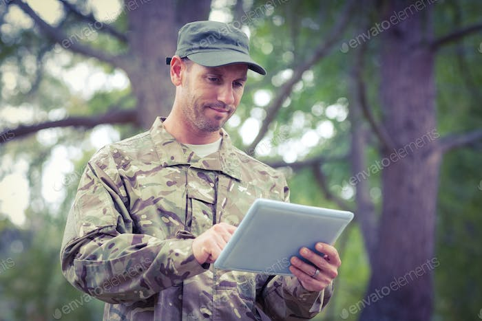 Soldier looking at tablet pc in park on a sunny day