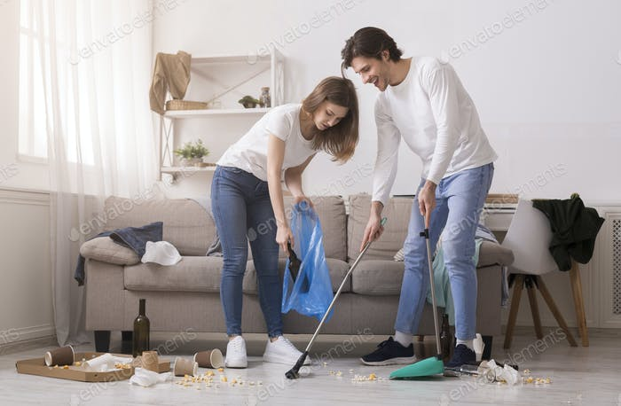 Couple Cleaning Messy Room After Party, Sweeping Floor And Collecting Garbage