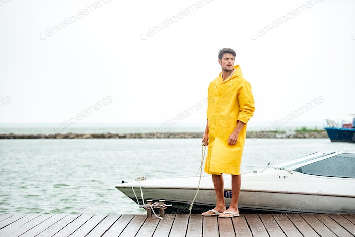 Handsome sailor in yellow cloak standing at the pier