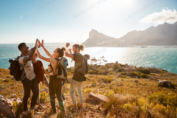 Young adult friends on a hike celebrate reaching a summit near the coast, full length, side view