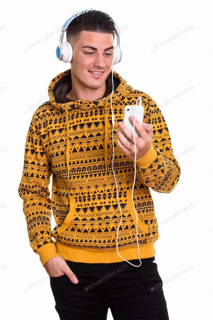 Young happy man smiling and listening to music while using mobil