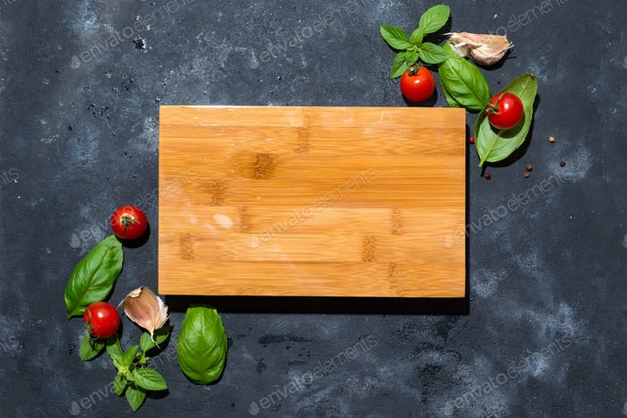 Ingredient for salad, tomatoes, garlic and basil in the form of a frame with a wooden board