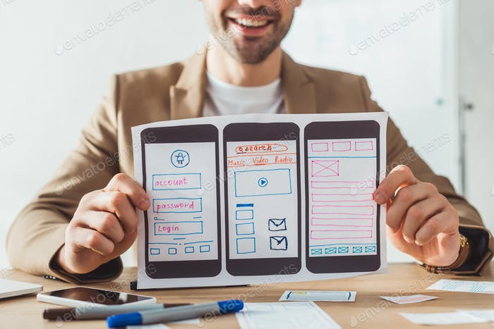 Vista recortada del diseñador sonriente que muestra bocetos de estructura alámbrica del sitio web móvil en la mesa