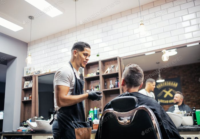 A man client talking to haidresser and hairstylist in barber shop.