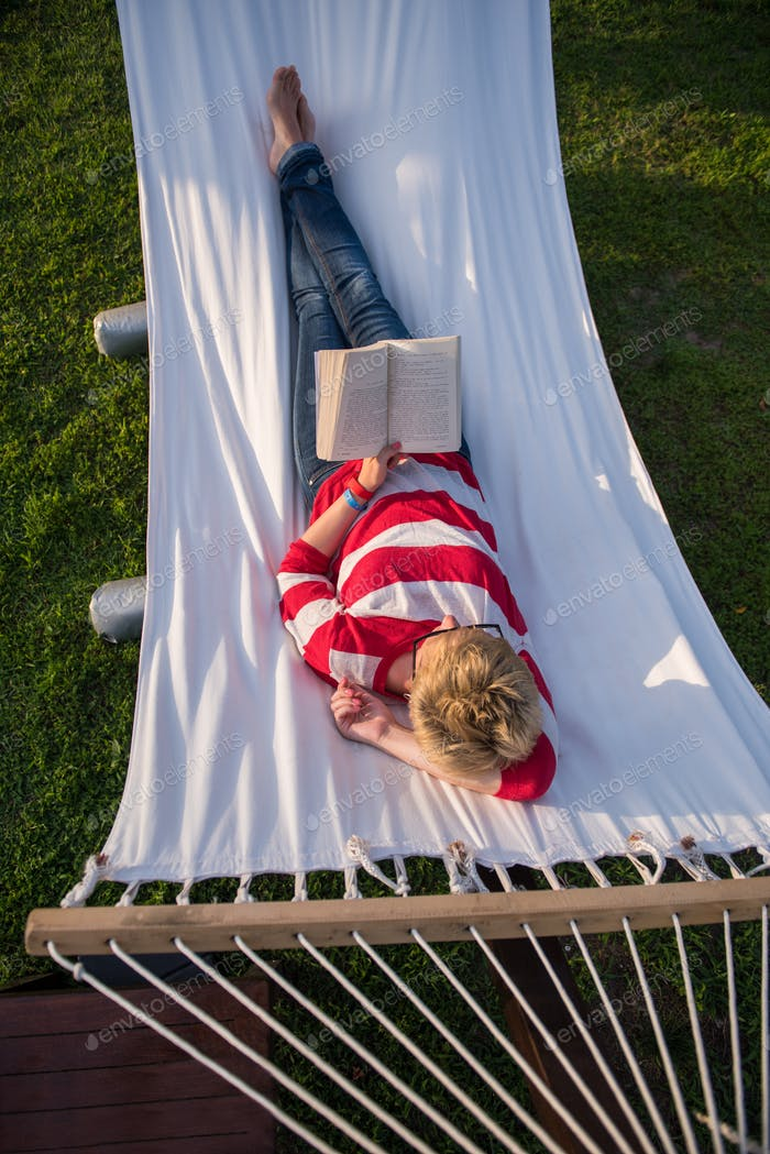woman reading a book while relaxing on hammock