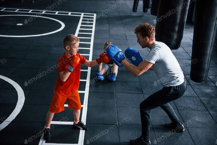 Young trainer teaches kids boxing sport in the gym