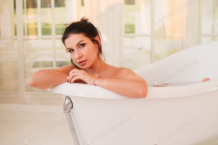 Beautiful young sexy girl with dark hair in bathtub