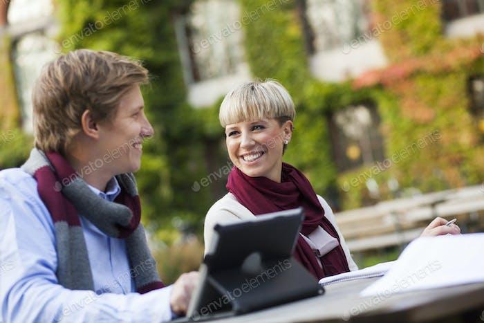Tilt Schuss von glücklichen Freunden mit digitalen Tablet sitzen am Tisch auf dem Campus