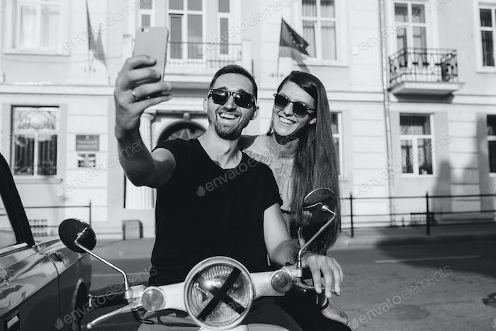 Cute couple make selfie on a scooter