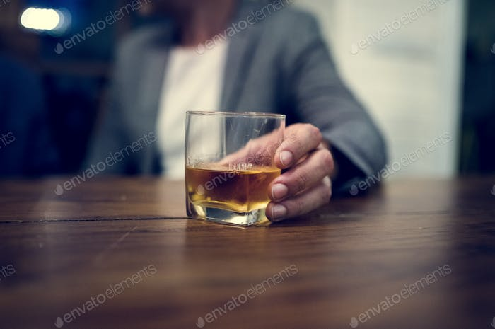 Shot of a person carrying a glass of alcohol