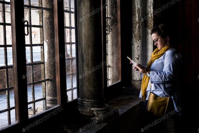 Woman wearing glasses standing at window of a historic building in Venice, Veneto, Italy.