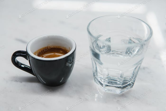 cup with coffee near a glass of water