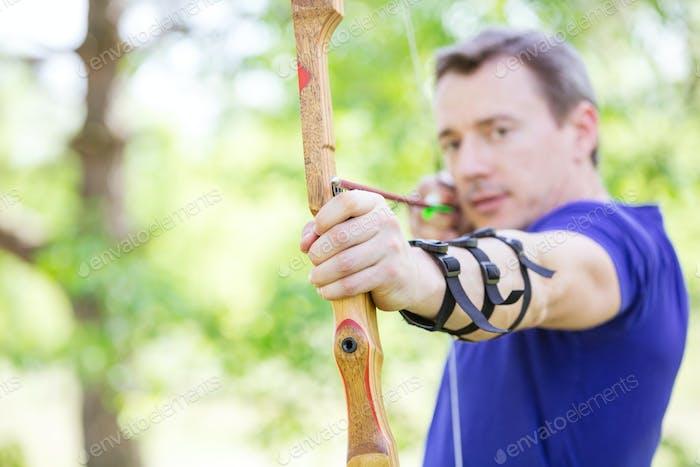 Bowman aiming arrow at target