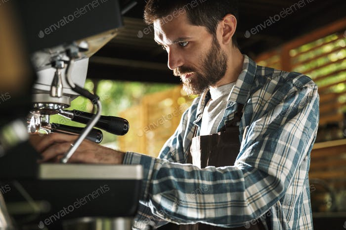 Image of happy barista man making coffee while working in cafe o