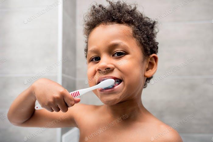 close-up portrait of beautiful african-american kid brushing teeth
