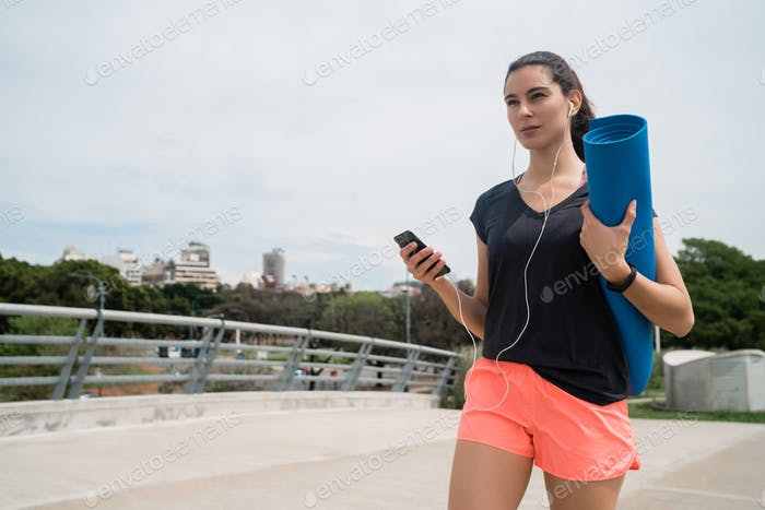 Athletic woman holding a training mat.