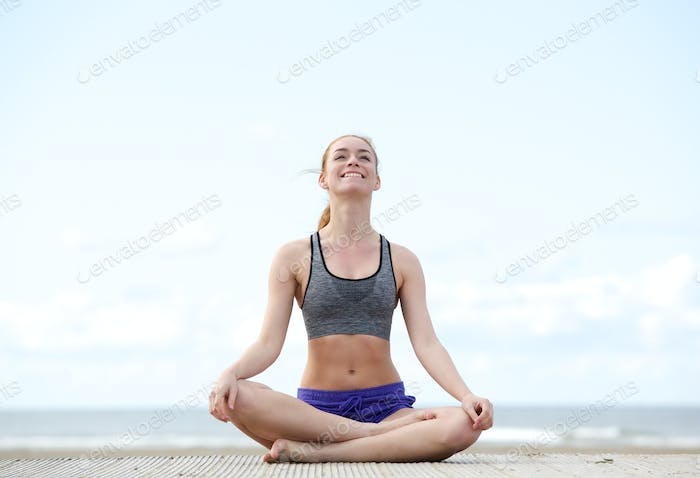 Woman sitting in yoga position and smiling outdoors