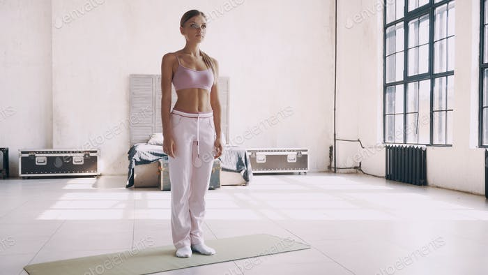 Yoga at home. A girl in pink sports clothes makes asanas at home.
