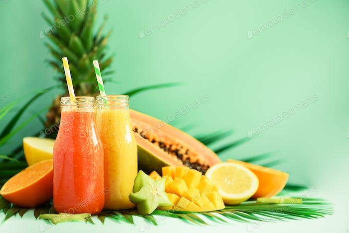 Juicy papaya and pineapple, mango, orange fruit smoothie in two jars on turquoise background. Detox