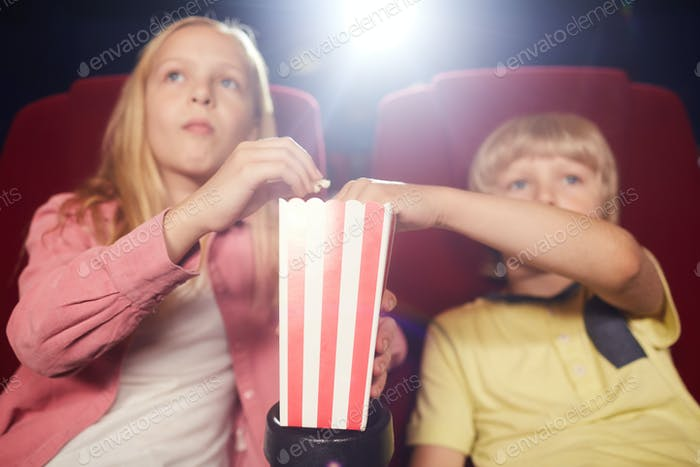 Children Eating Popcorn in Cinema