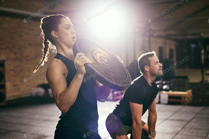 Two sportsmen having workout with weight disks