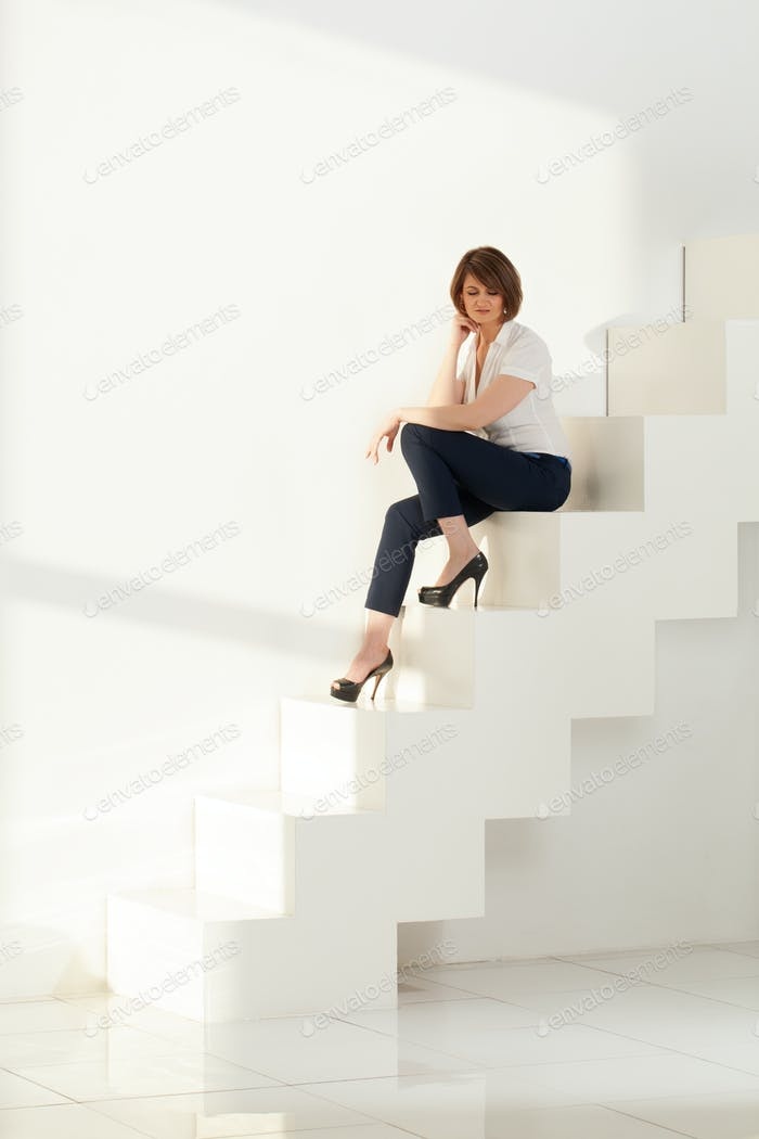 Adult businesswoman sitting on steps and looking down