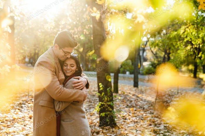 Image of young happy couple smiling and hugging in autumn park