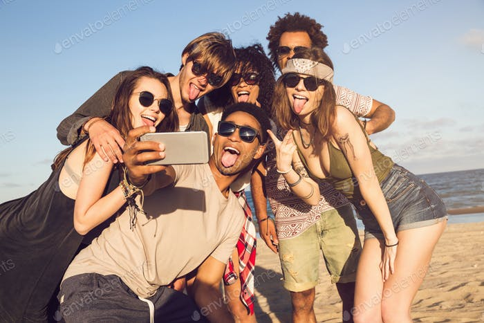Cheerful multiethnic friends taking selfie at beach on sunny day