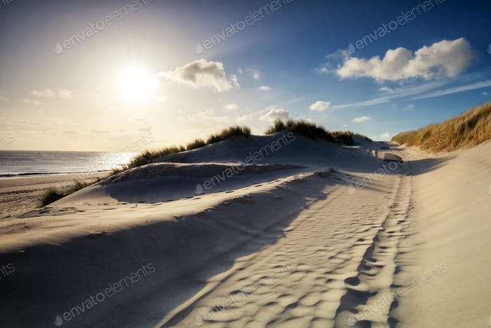 walking between sand dunes in sunshine