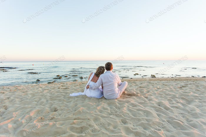 Young love couple sitting together on beach, rear view