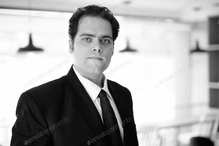 Iranian businessman relaxing at home in black and white
