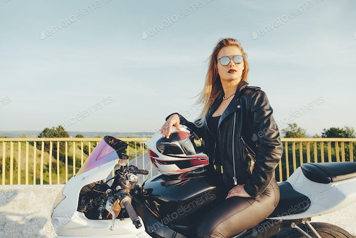 Biker girl in a leather clothes on a motorcycle