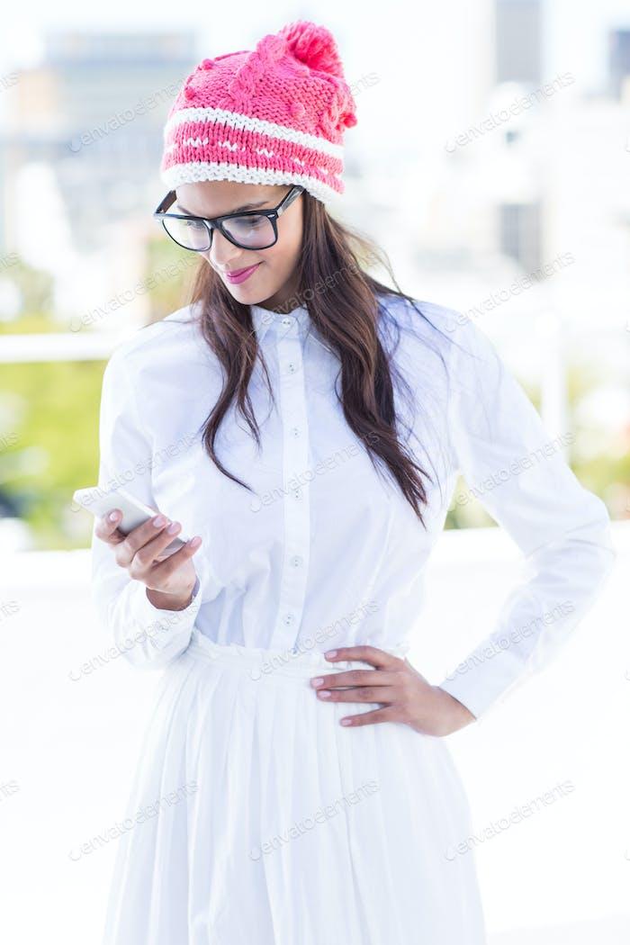 Pretty brunette using her smartphone outside