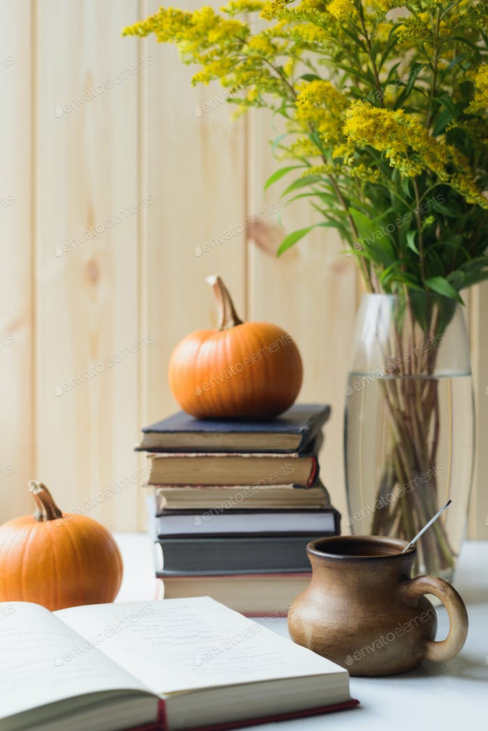 autumn still life with books, pumpkins, cup, solidago bouquet