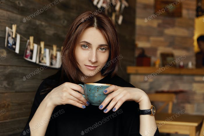 People, leisure and lifestyle concept. Beautiful European brunette girl dressed in elegant black clo