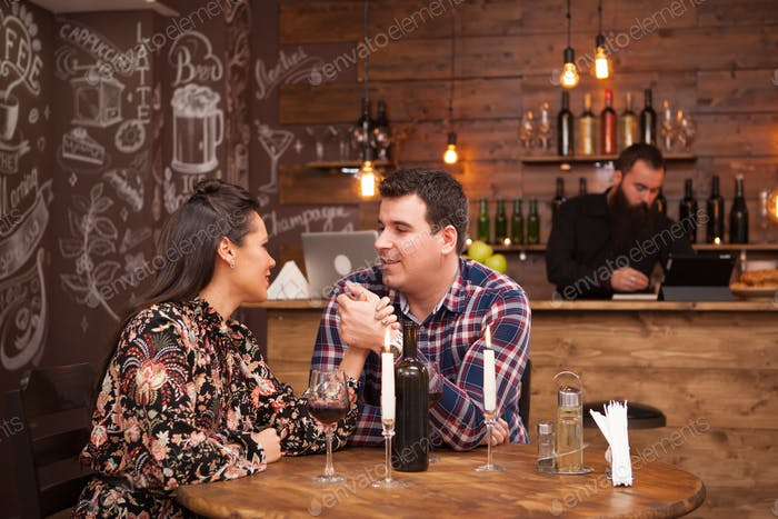 Couple on a date sitting in a hipster pub drinking red wine