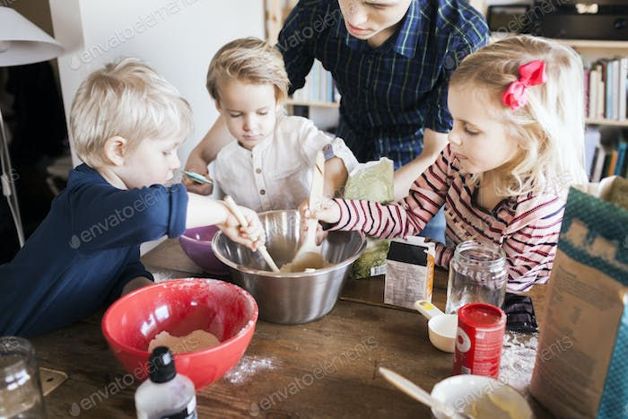 Children mixing ingredients together at home