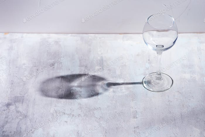 Wine glass with sun hard light shadow reflection on stone background