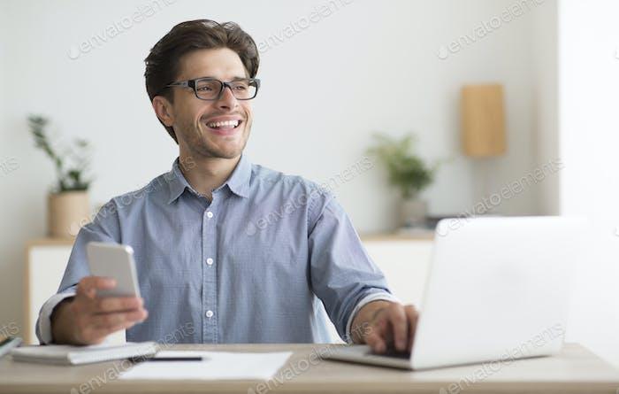 Mann mit Smartphone sitzt vor Laptop im Büro