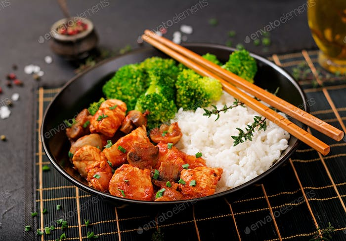 Pieces of chicken fillet with mushrooms stewed in tomato sauce with boiled broccoli and rice.