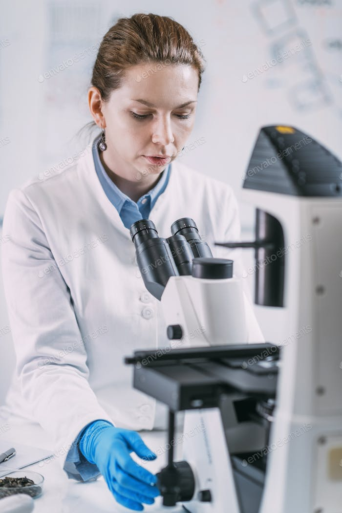 Portrait of Young Female Archaeologist with Microscope