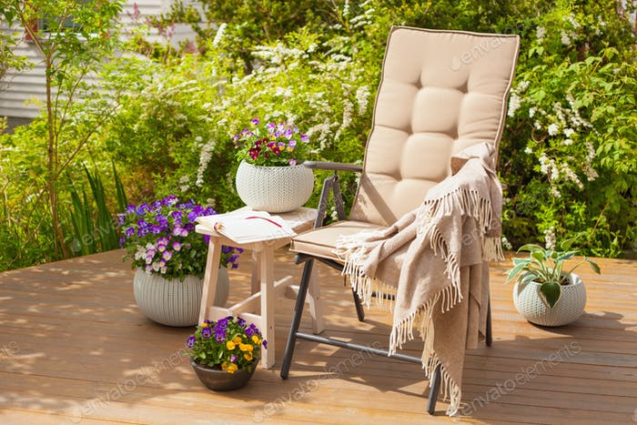 garden chair on terrace and pansy flowers