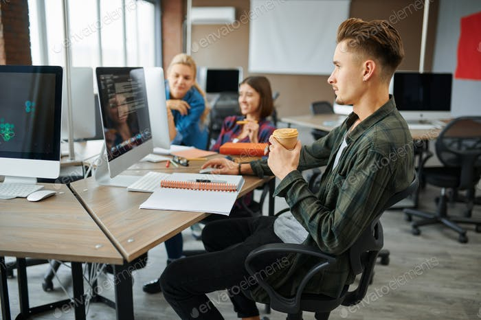 Young IT specialists works on computers in office