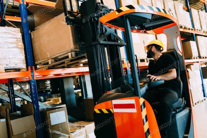Lagerarbeiter, der Logistikarbeit mit Gabelstapler leistet