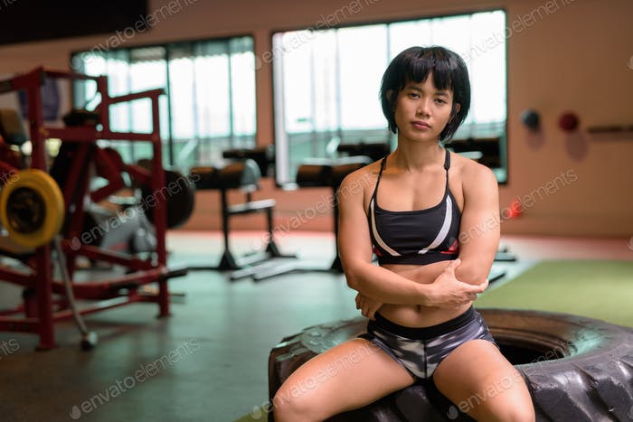 Junge schöne asiatische Fitness Frau sitzen im Fitness-Studio