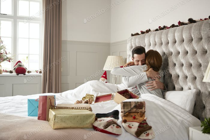Couple Hugging In Bed At Home As They Exchange Gifts On Christmas Day